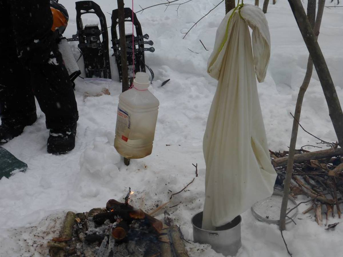 Melting snow over a fire in a pillowcase and boiling water inside a plastic bottle.