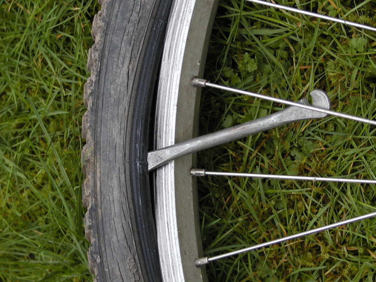Hook the tire lever under a spoke
