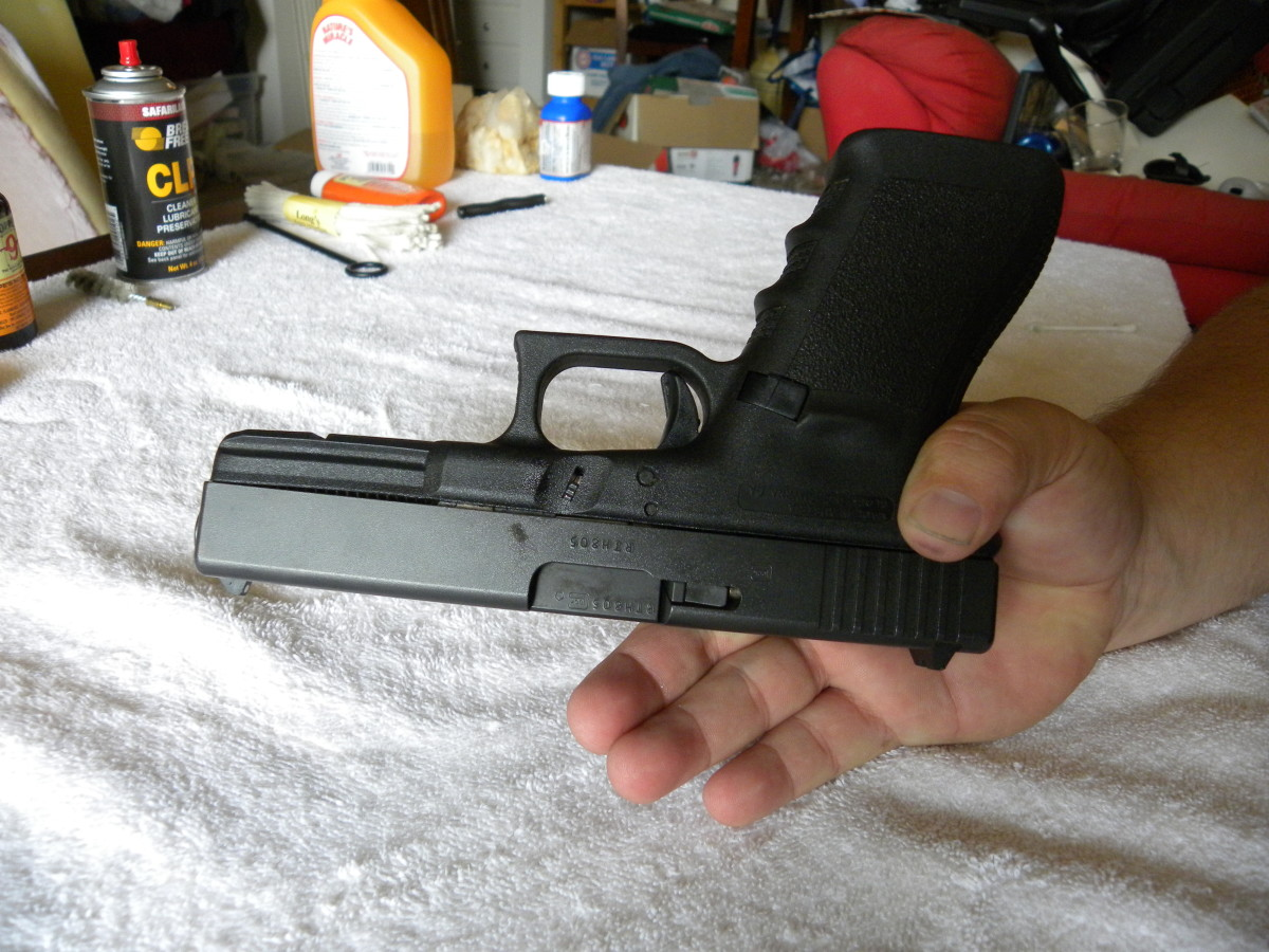 Flip the pistol upside down, and wrap your thumb around the curve at the top of the frame grip. Then, wrap your other fingers around the slide, getting a firm grip on it.