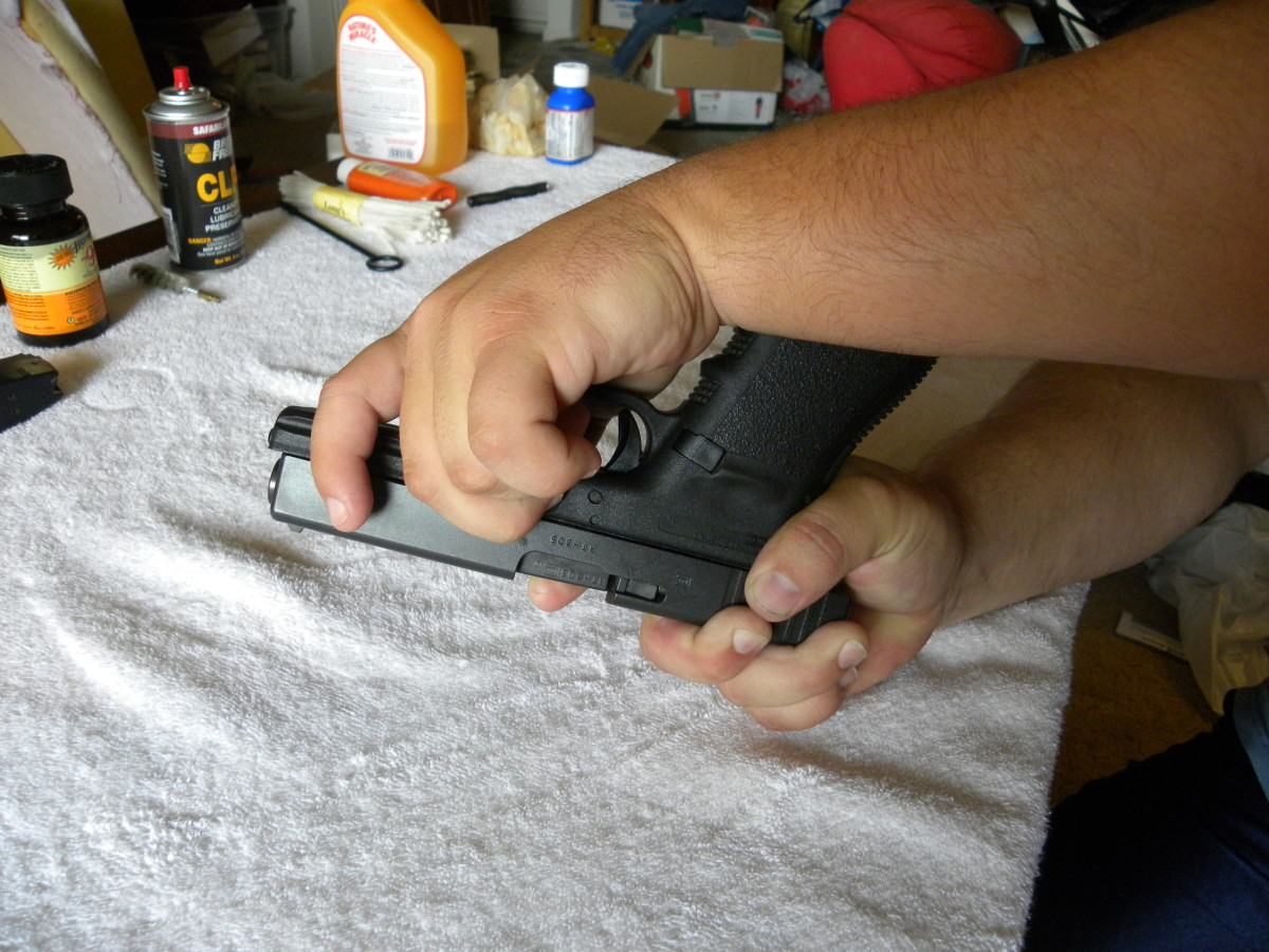 Just above the edge of the trigger guard is a rectangular pin that can be slid upwards, releasing the slide from the frame. With thumb and forefinger, grip the pin, and slide it upwards, holding it in place there.