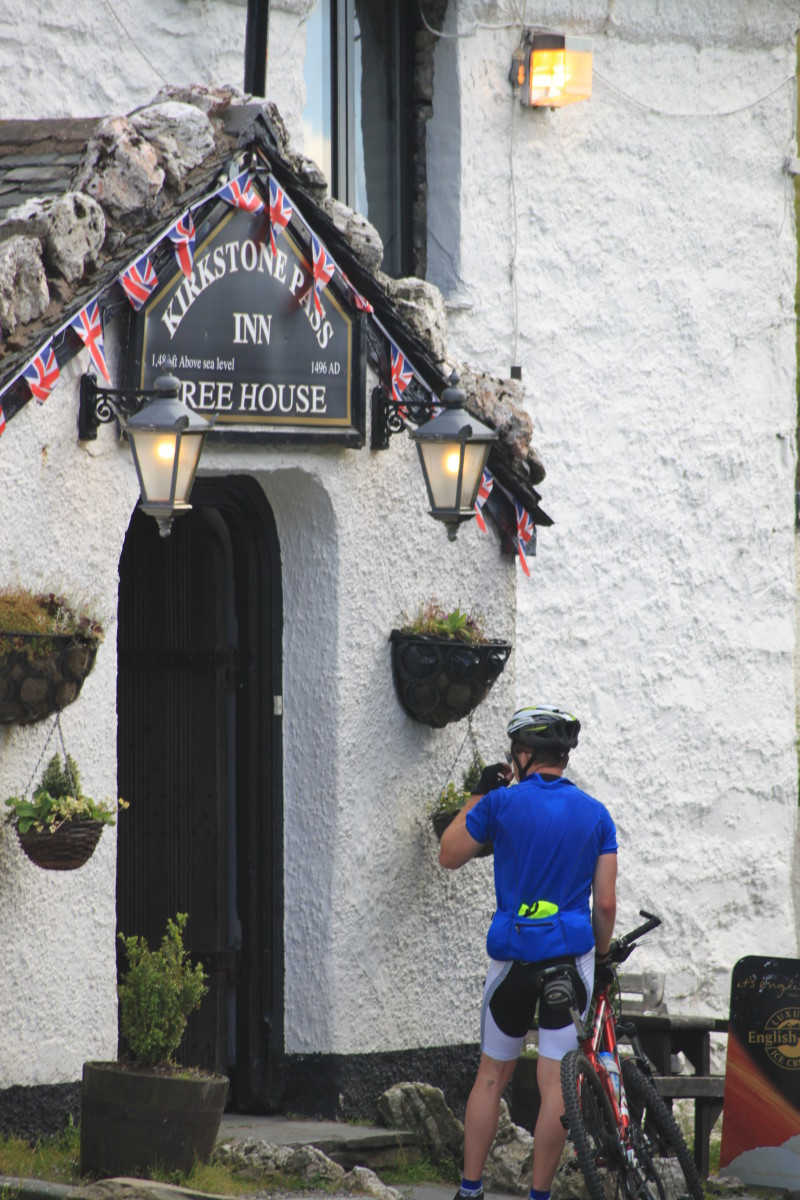 A cyclist grabbing a drink outside the Kirkstone Pass Inn after complting the highest pass in the Lake District