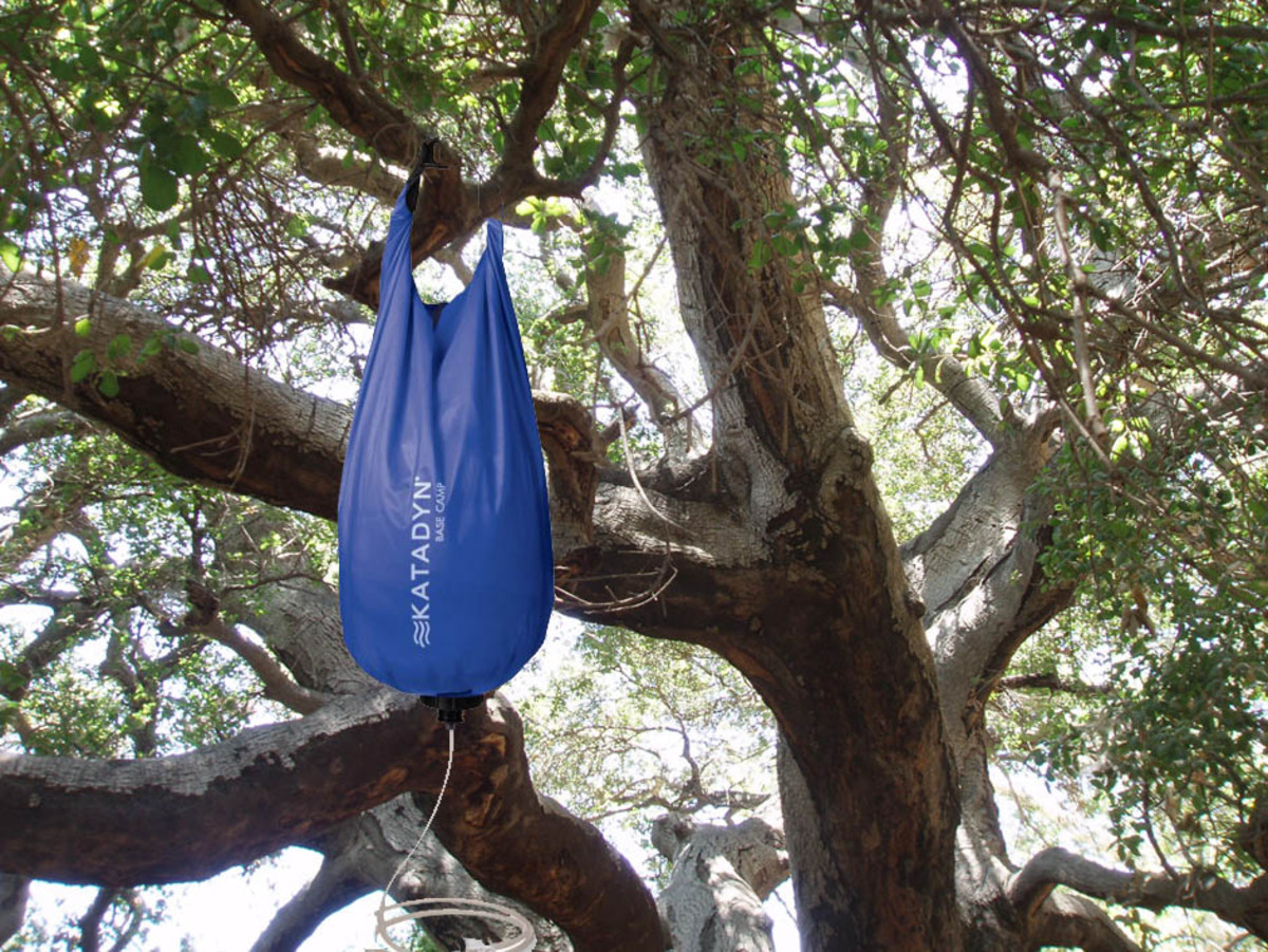 The gravity bag hangs from a tree branch, using the force of gravity to pull water through the filter.