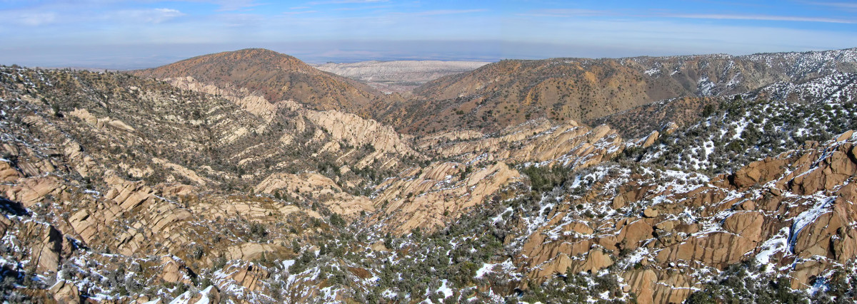 Devil's Punchbowl panorama, looking southeast. The Pinyon Earthquake Fault lies to the left. The Punchbowl Fault is on the right - note the different thrust to the cliffs. The San Andreas Fault is through the V between the furthest mountains.
