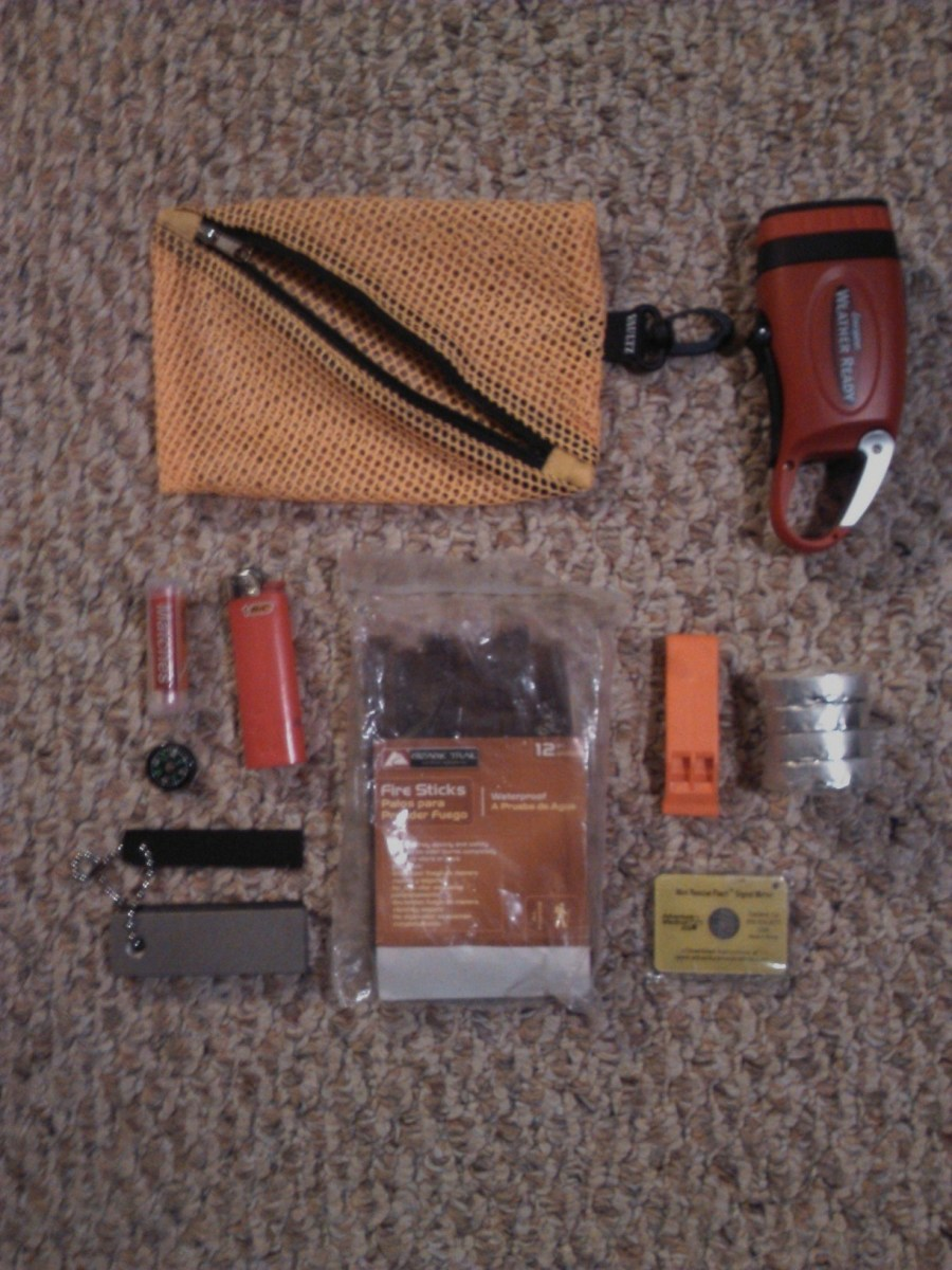 From left to right: crank flashlight, waterproof matches, lighter, flint with striker, fire sticks, whistle, tealights and signal mirror.