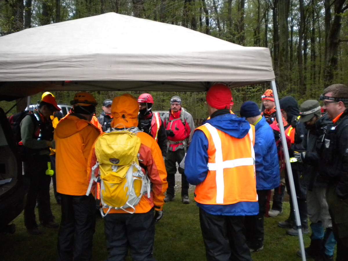 A SAR team briefing on a cold and rainy day for a search that will extend into the night.