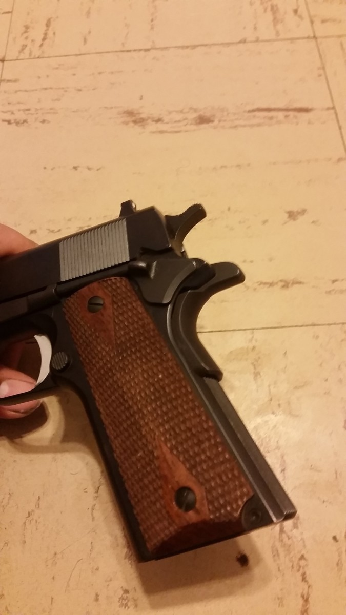 Showing off the nice fit of the walnut grips and the flat main spring housing. You can also see the A1 style trigger and grip safety.