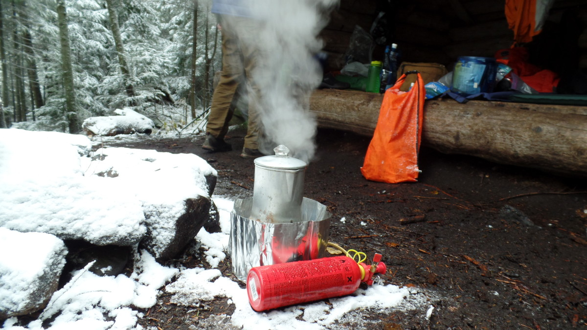 Making coffee with a percolator on a camp stove.