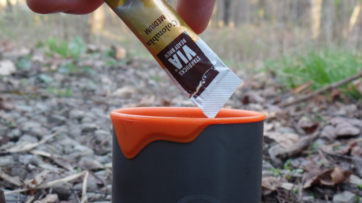 Adding Starbucks Via Instant coffee to a cup while camping.