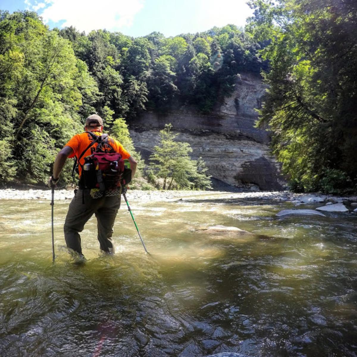 Using trekking poles to cross a river.