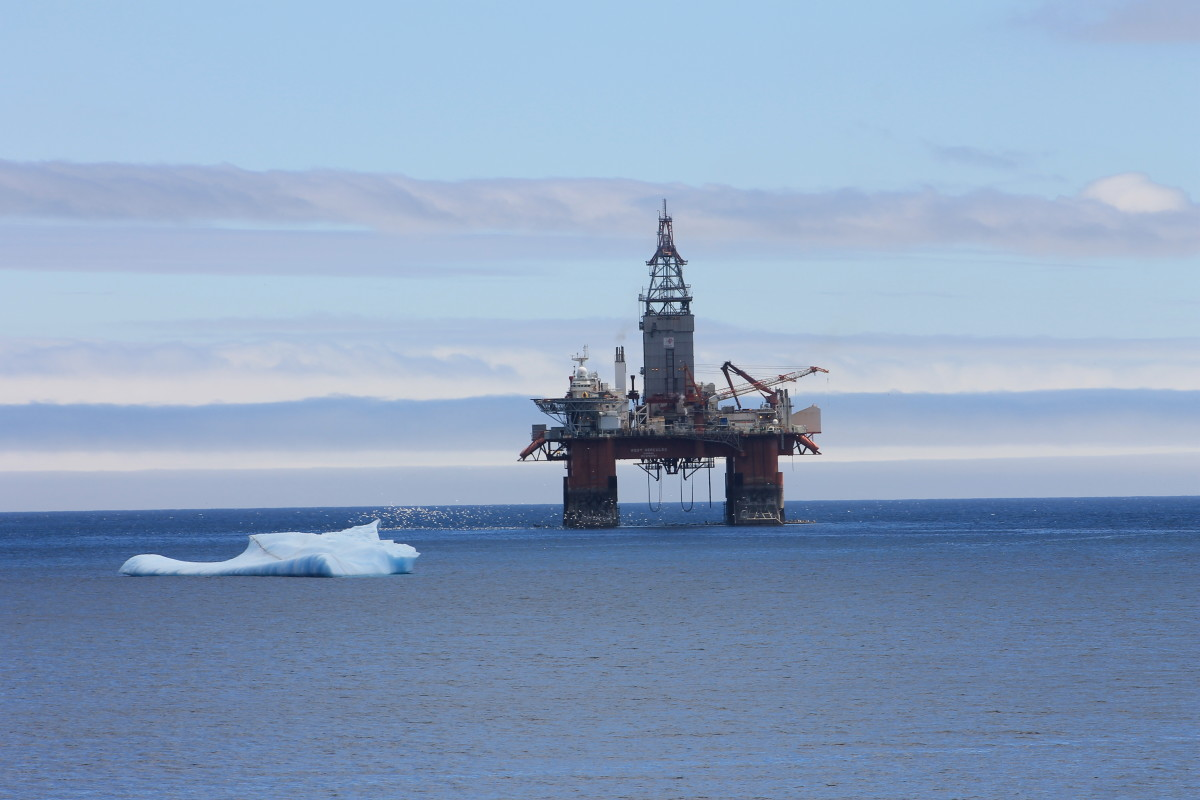 An iceberg drifts past an oil rig in the bay, Bay Bulls, NL.