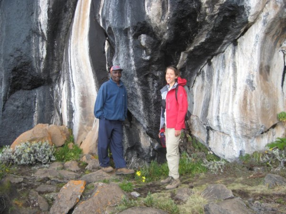 Standing next to Zebra Rocks with our guide, Abasi.  The stripes are caused by mineral-rich rainwater that flows over the rock face.