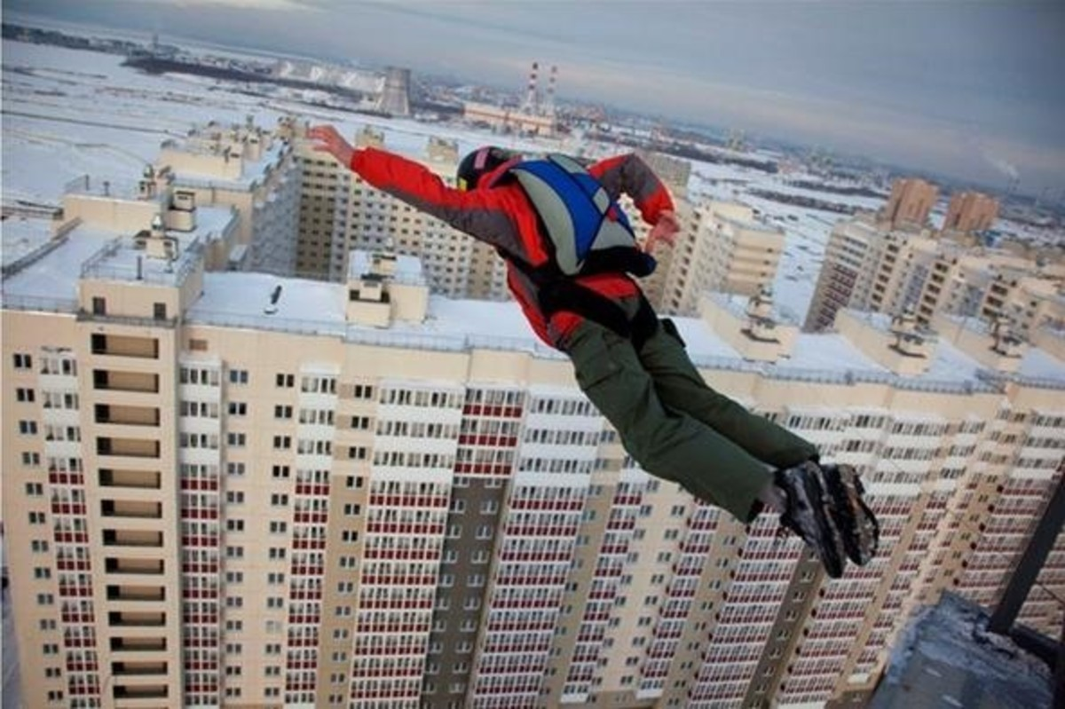 BASE jumper doing a low building exit in Russia, ready to open his parachute upon jumping.