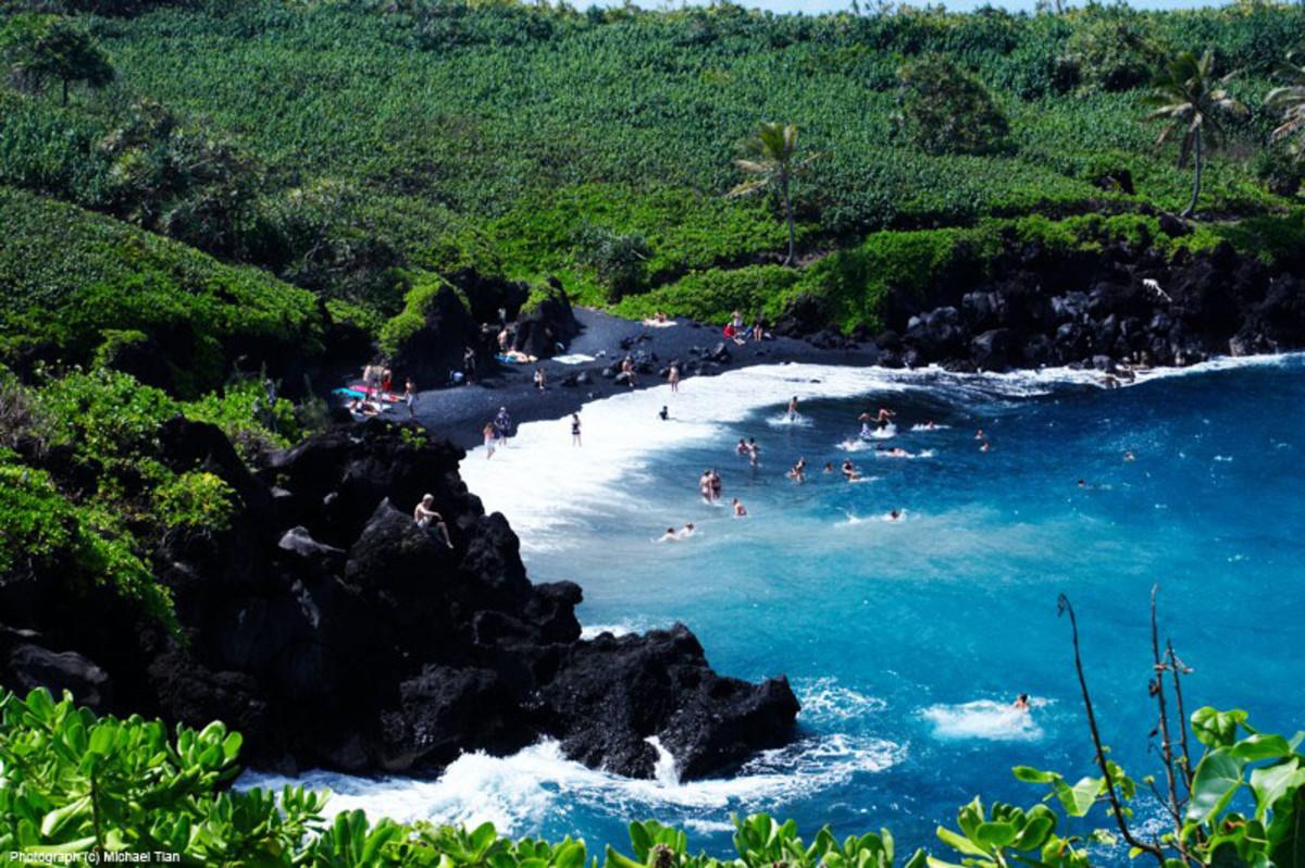 Swimmers enjoying the beautiful black beach at Wai'anapanapa State Park on Maui, HI