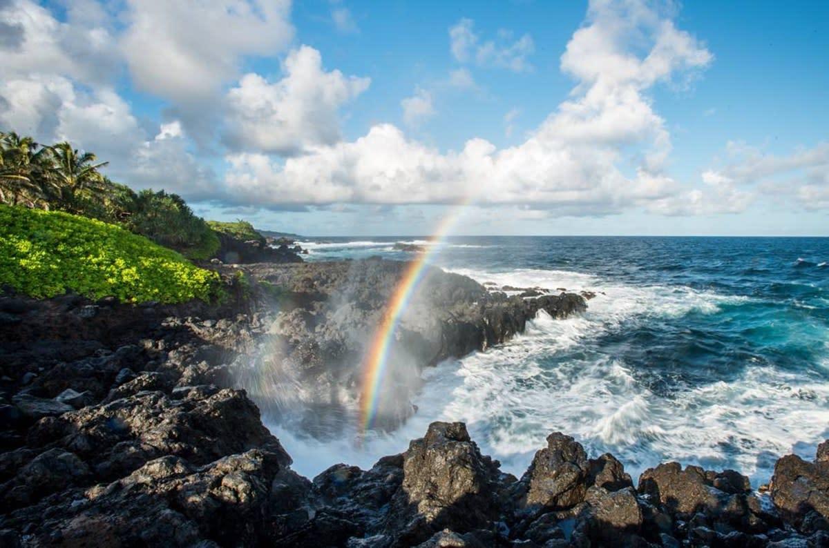 A rainbow forms in the mist of the ocean crashing on a rocky shore, in the Kipahulu area of Haleakala National Park, Maui, HI