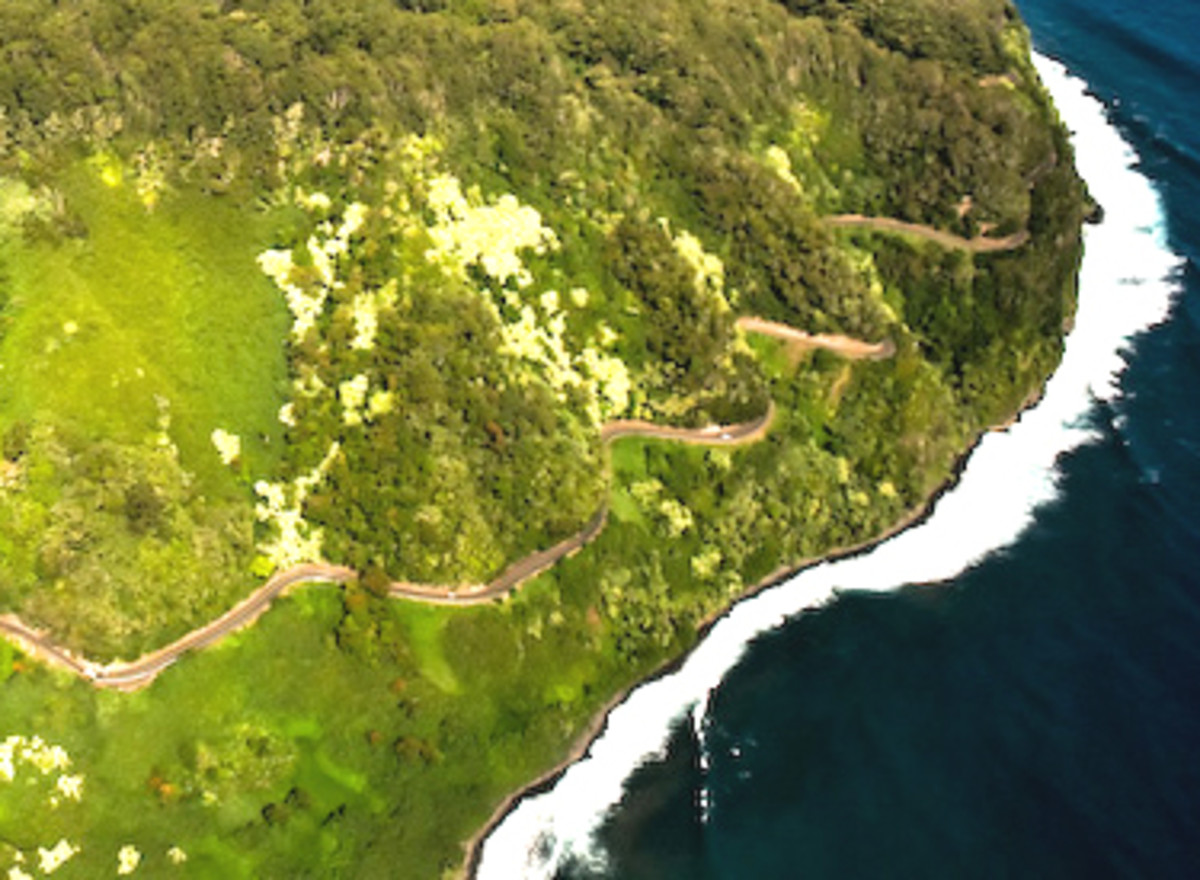 An aerial view of the Hana Highway gliding 68 miles along the shore of Maui, with beautiful views of the surf below, crossing many bridges over creeks headed for the sea.