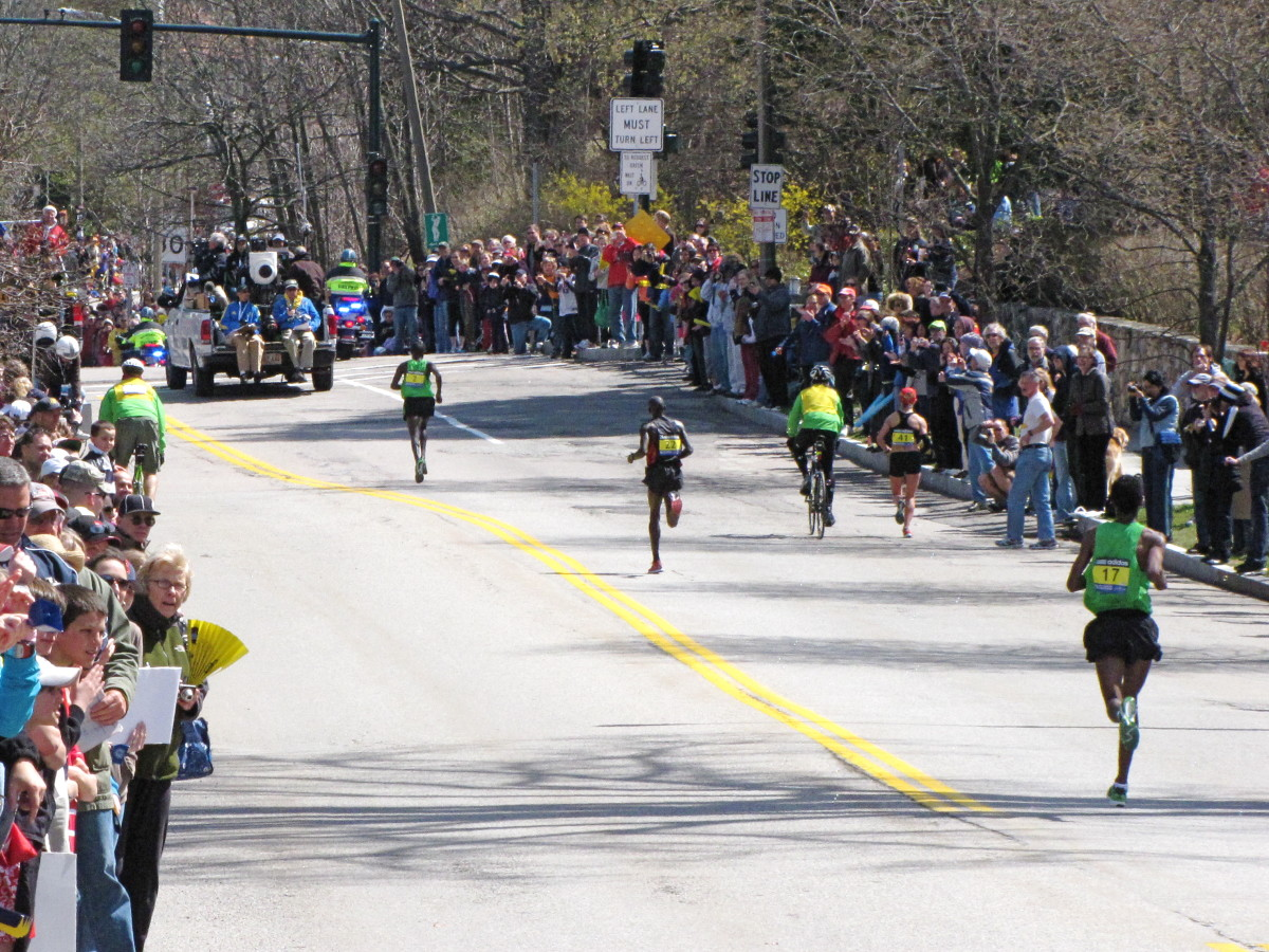 Top 3 men heading up Heartbreak Hill in what would be a record time for winner Geoffrey Mutai of Kenya in 2:03:02  at the  2011 Boston Marathon.