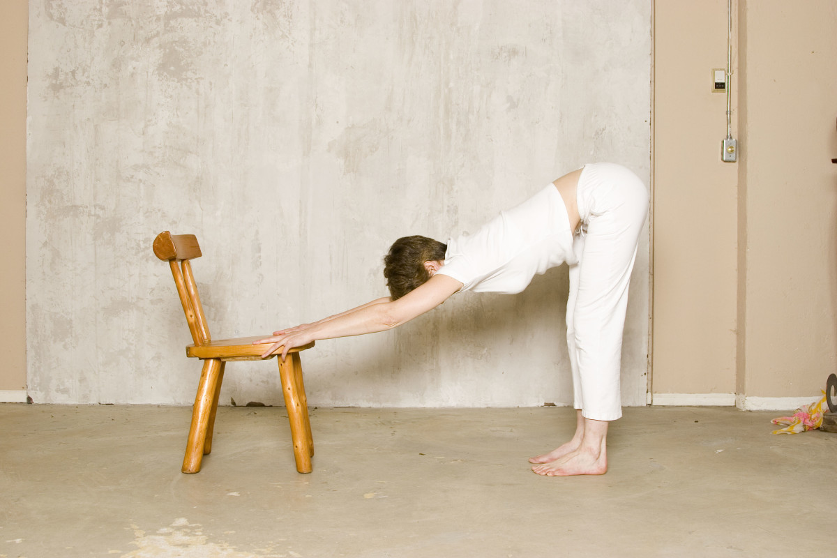 Supported Downward Facing Dog on a Chair releases tension from the lower back and shoulders, and stretches the back of the legs.
