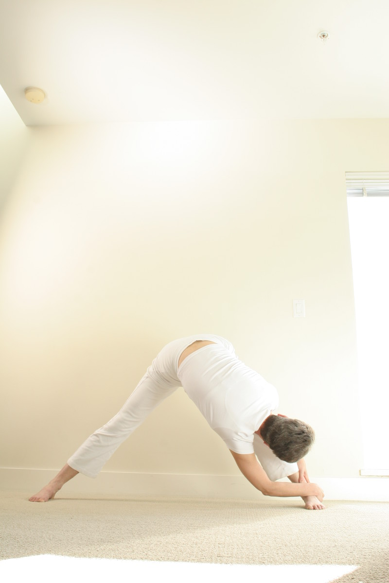 Wide legged forward fold to the side deepens the stretch inside the thighs and down the outside of the ribs and arm.