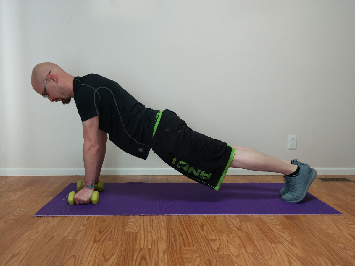 To do a pushup to plank row, assume a pushup position while placing your hands on the dumbbells, arms extended, and chest aligned with the dumbbells.