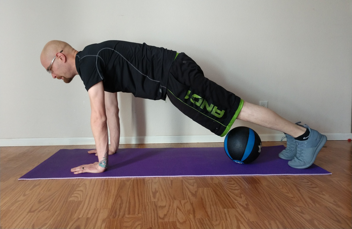 Start in plank position with the medicine ball under your shins.