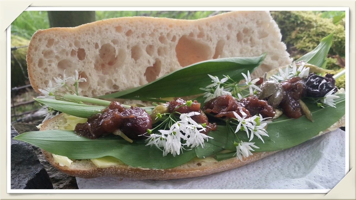 A sourdough baguette filled with wild garlic leaves and flowers, pickled wild garlic buds, wild plum sauce, and a few olives.