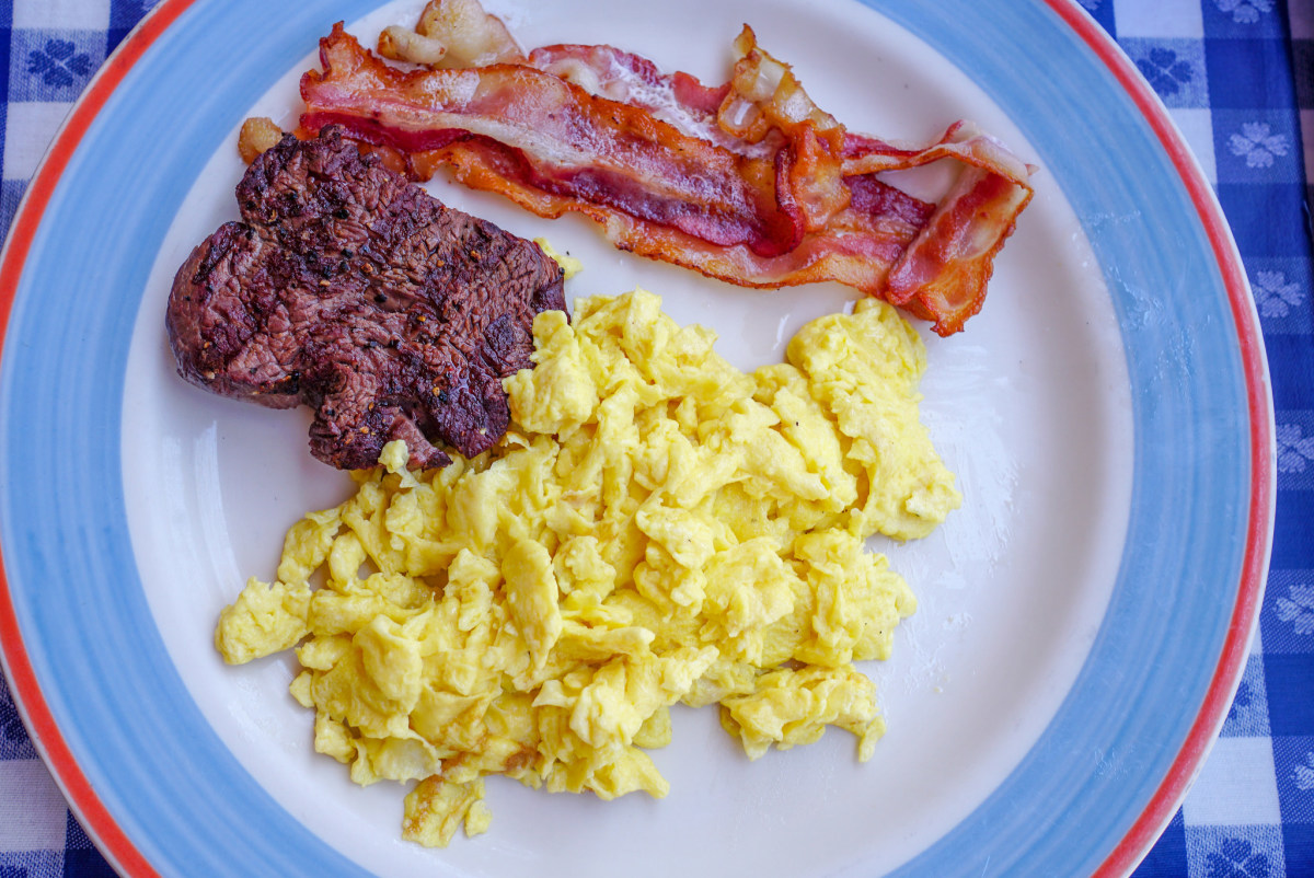 A ketogenic breakfast consisting of scrambled eggs, fried bacons, and animal protein.
