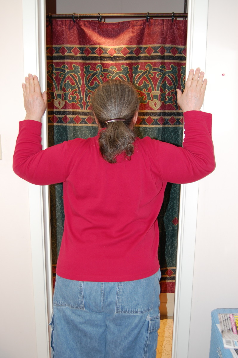 Place hands on door frame, with elbows even with shoulders, and lean into door opening