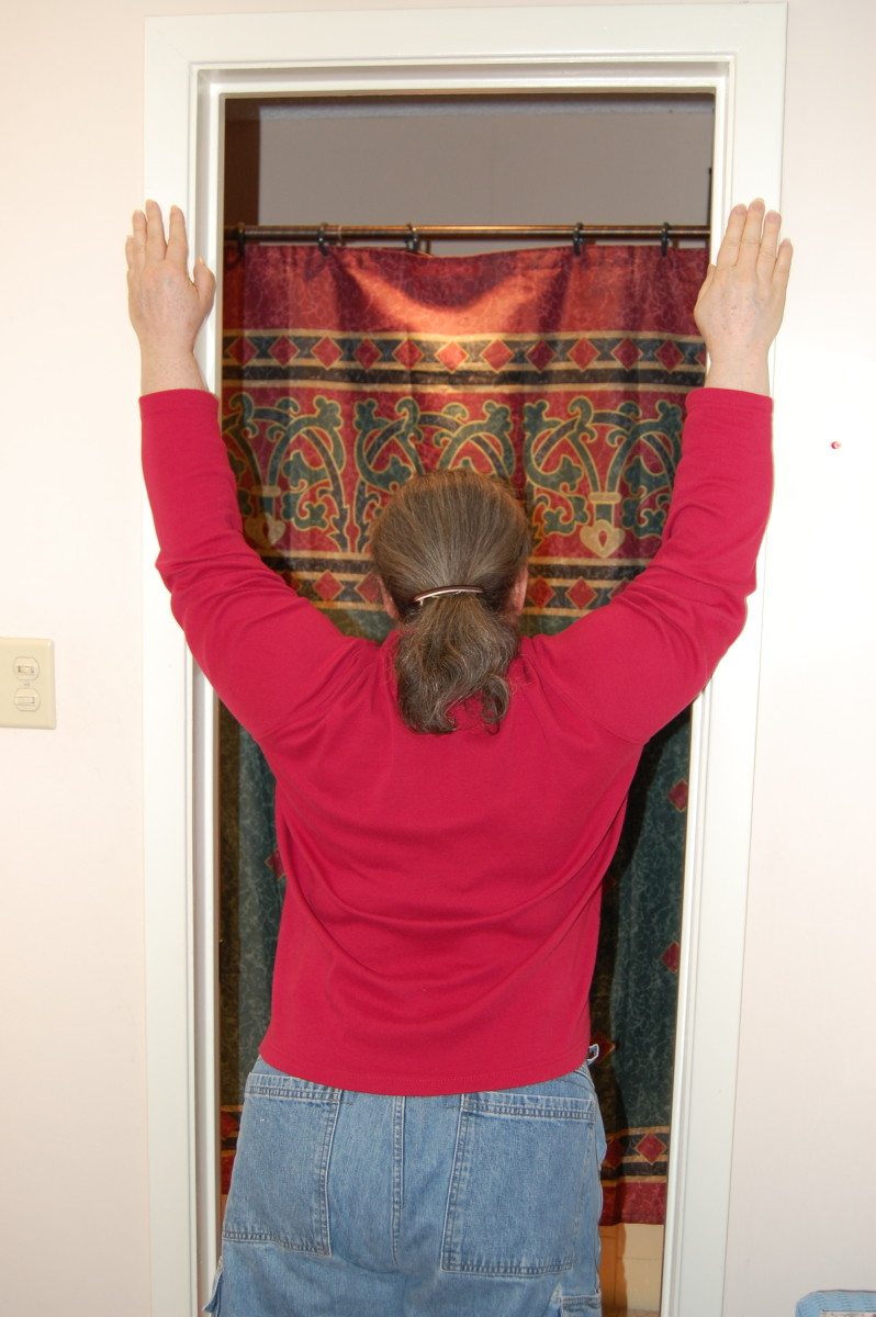 Place hands on door frame, with elbows above shoulders, and lean into door opening