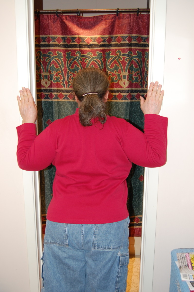 Place hands on door frame, with elbows below shoulders, and lean into door opening