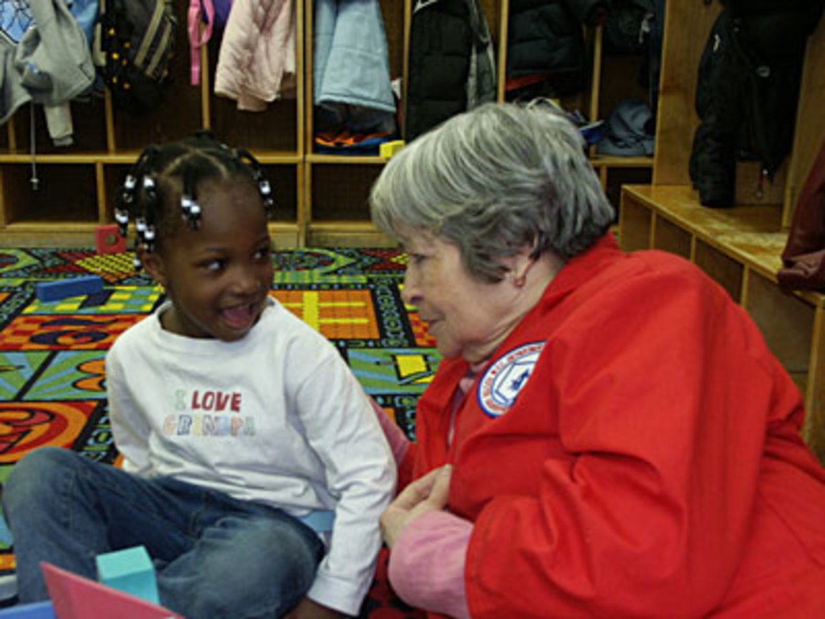 Volunteer helping child read