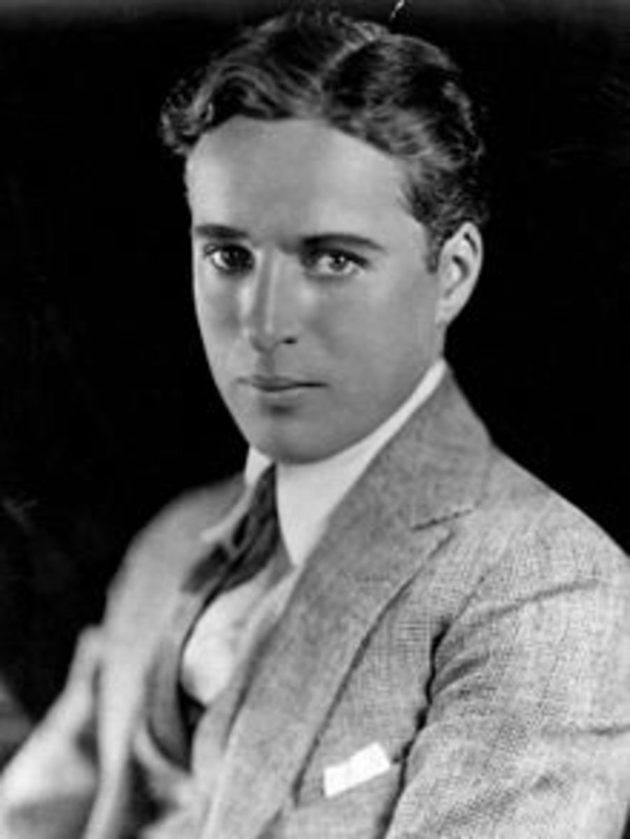 black and white portrait of Charlie Chaplin in his youth dress in a white shirt tie and suit coat circa 1920 publicity photo