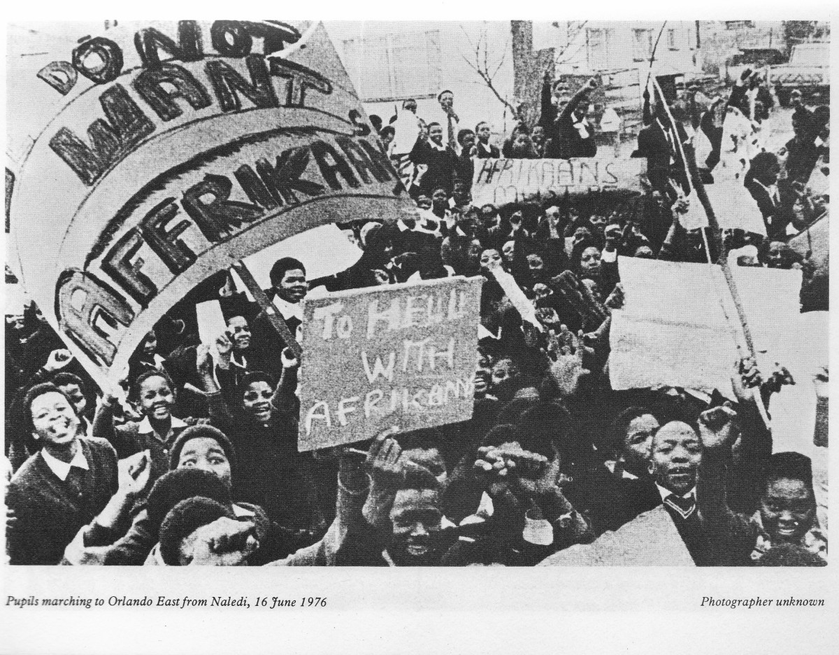 Students within the main body marching to the stadium and exuberantly showing placards which state how the students felt about the Afrikaans issue in 1976