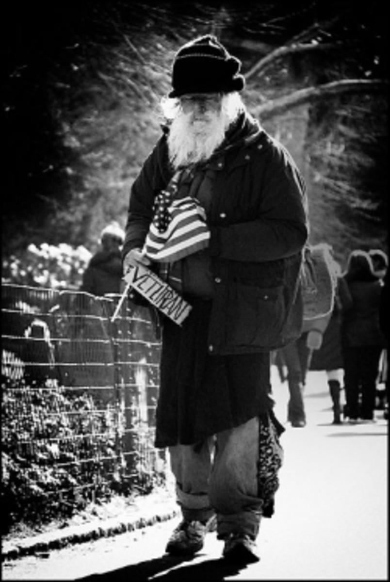 Elderly homeless veteran carrying an American flag