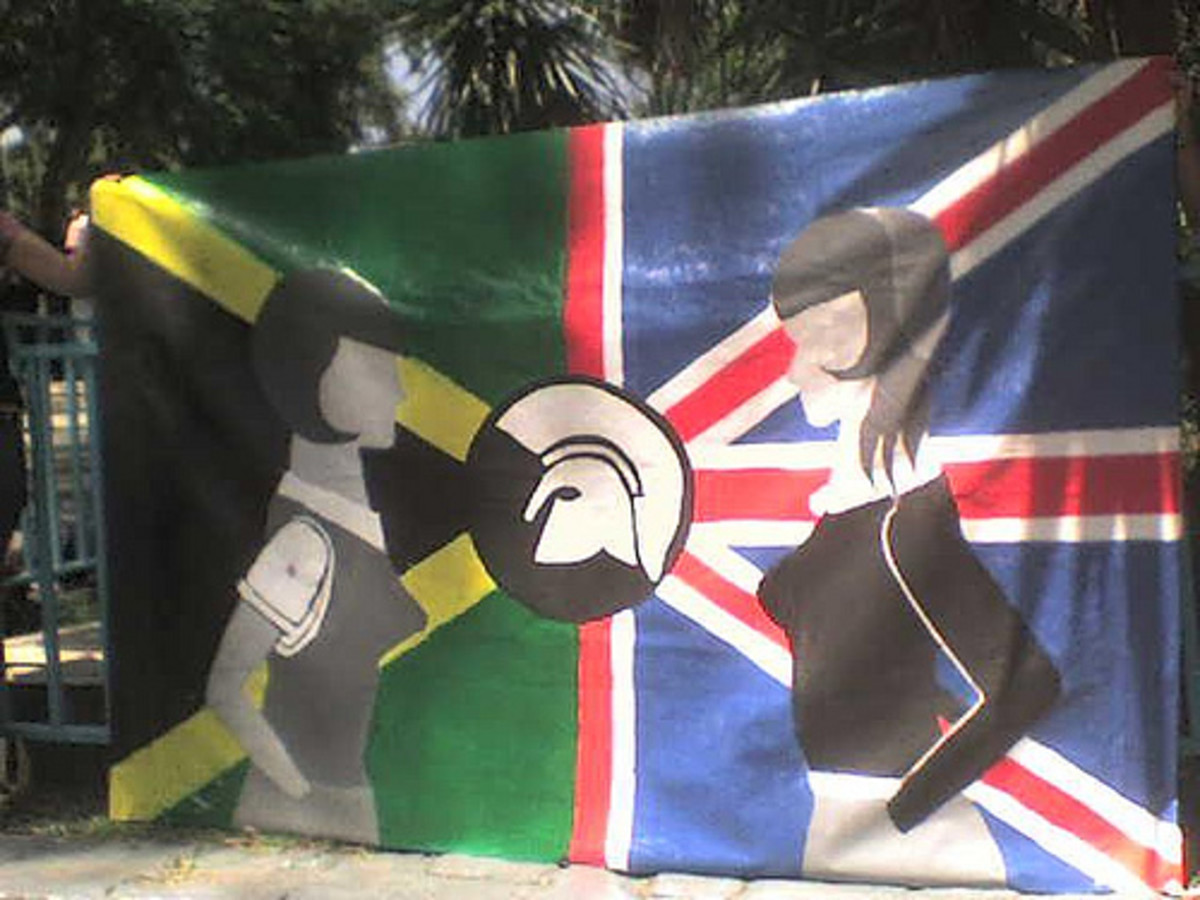 Jamaican and British flag with the Trojan Records helmet uniting them. On the flag, a white and black skinhead girl stand across from each other.