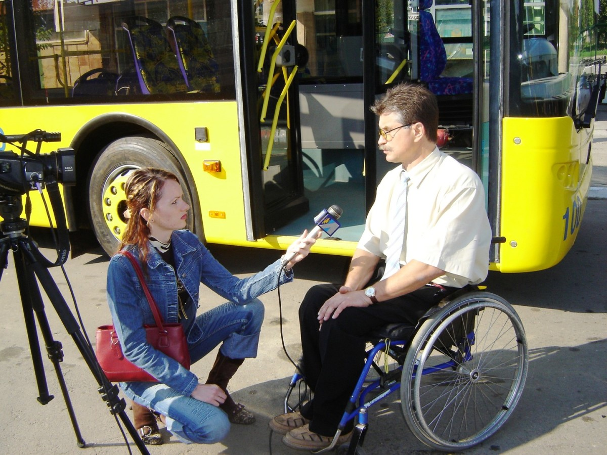 A reporter interviewing a man in a wheelchair.