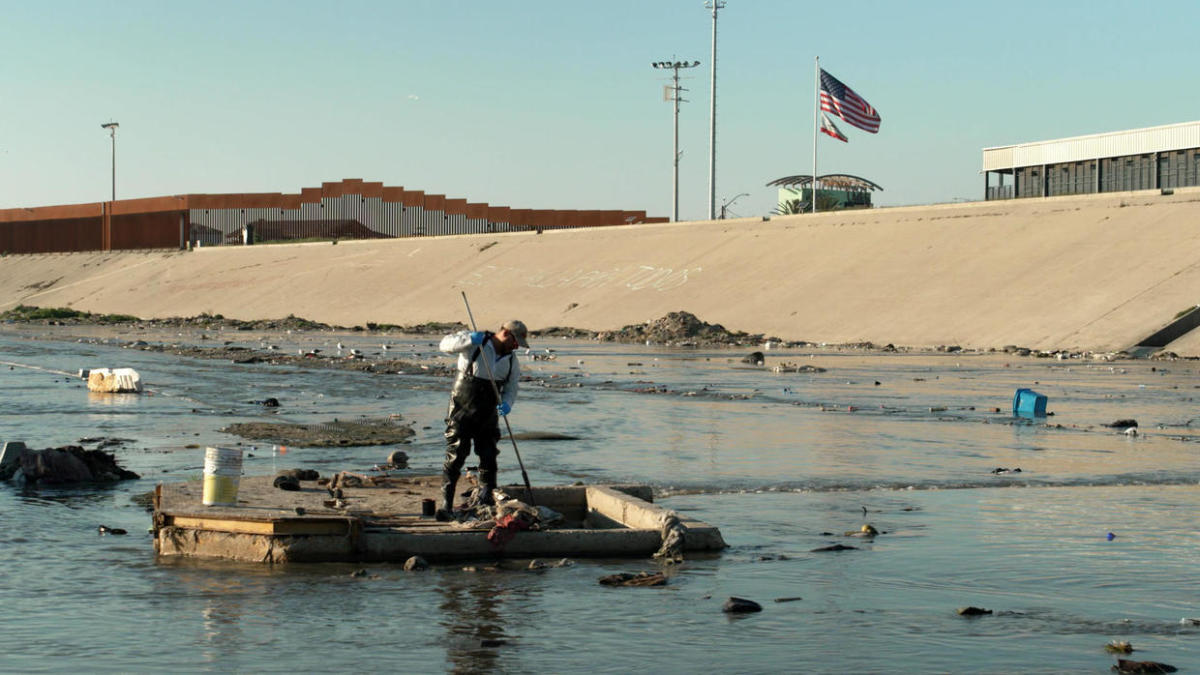 Worker unclogs the Tijuana River