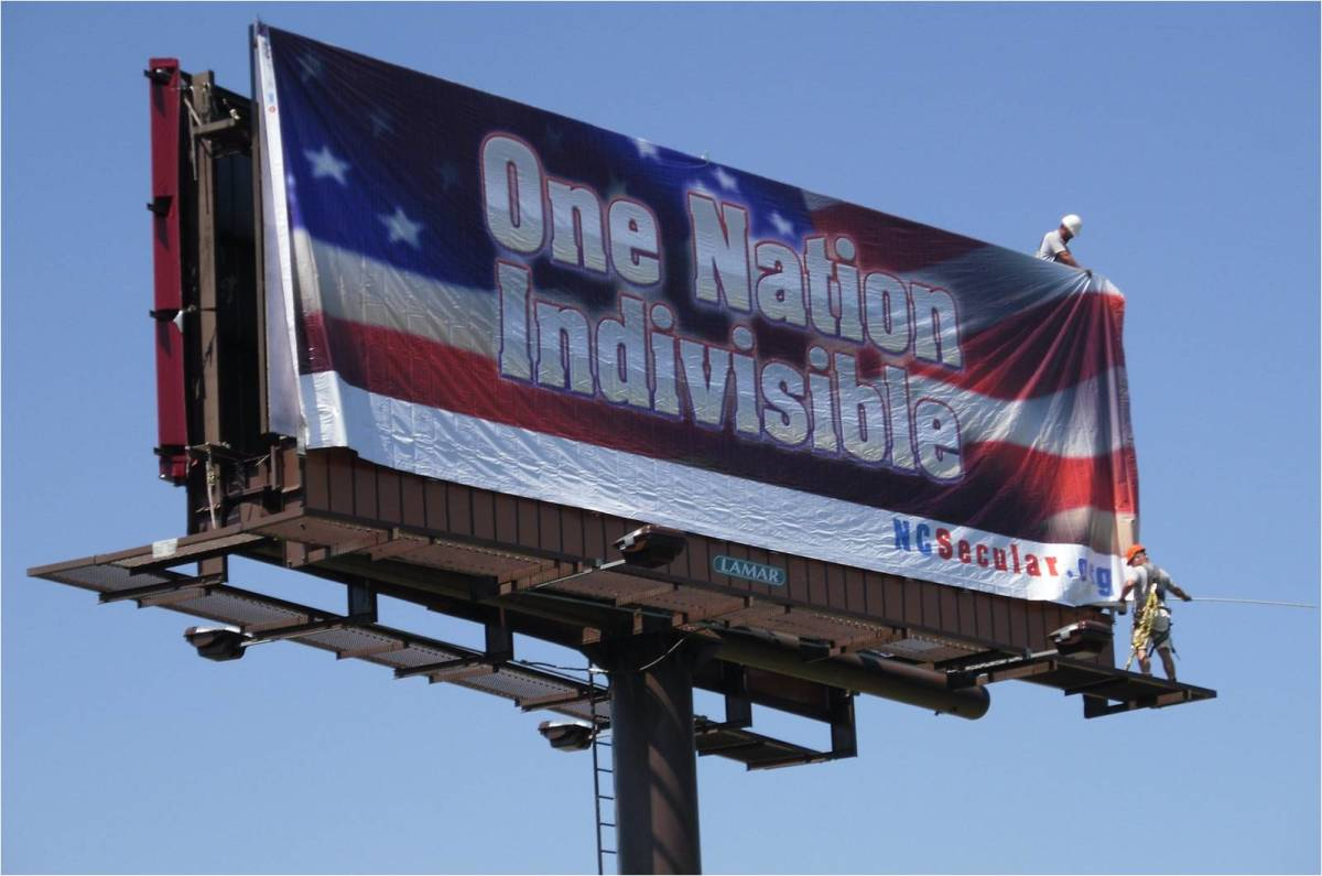 "A billboard proclaims ""One Nation Indivisible"" against a backdrop of an American flag."