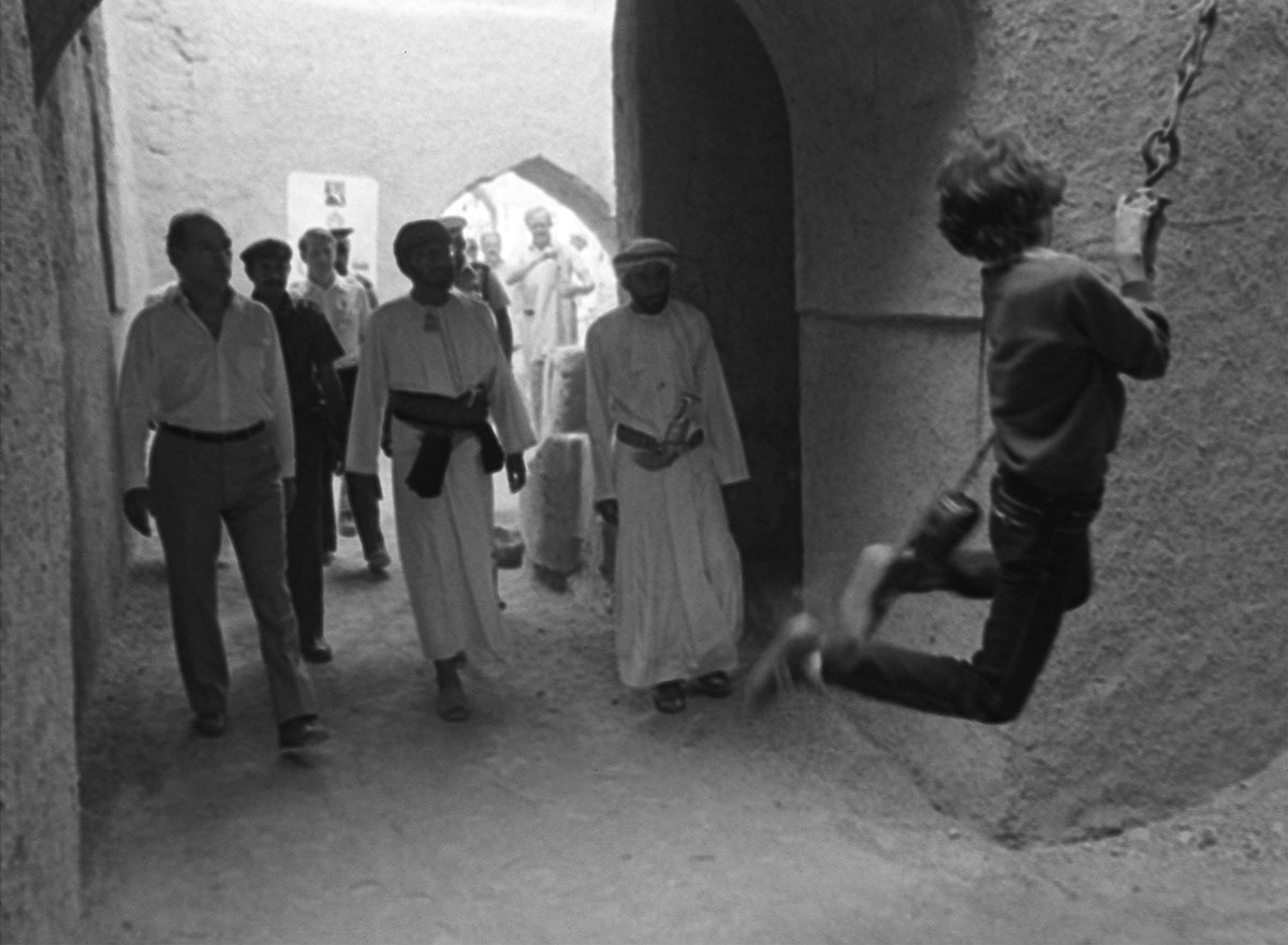 Pierre Trudeau, left, watches as his 11-year-old son Justin swings on a chain during a tour of an old fort in the Omani town of Nizwa (Dec 2, 1983)