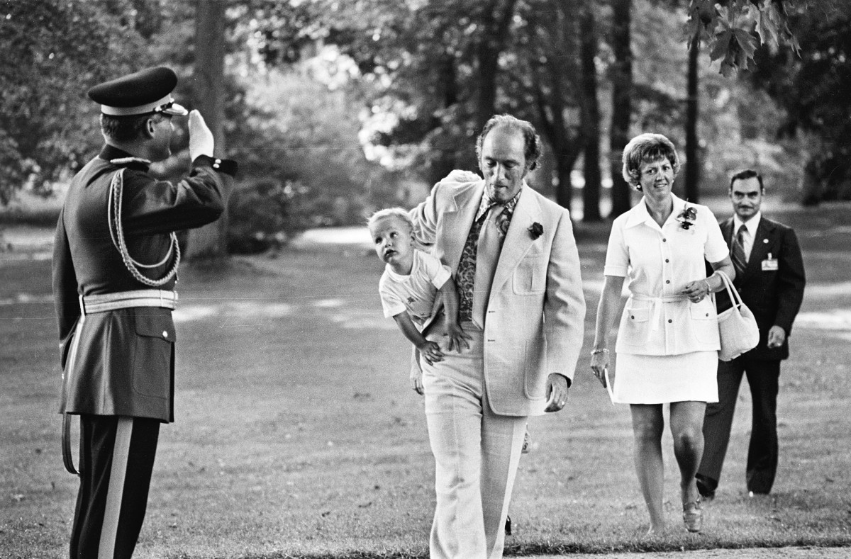 PM Trudeau arrives at a Garden Party at Government House with Justin under his arm, as an RCMP salutes (Aug 1973).