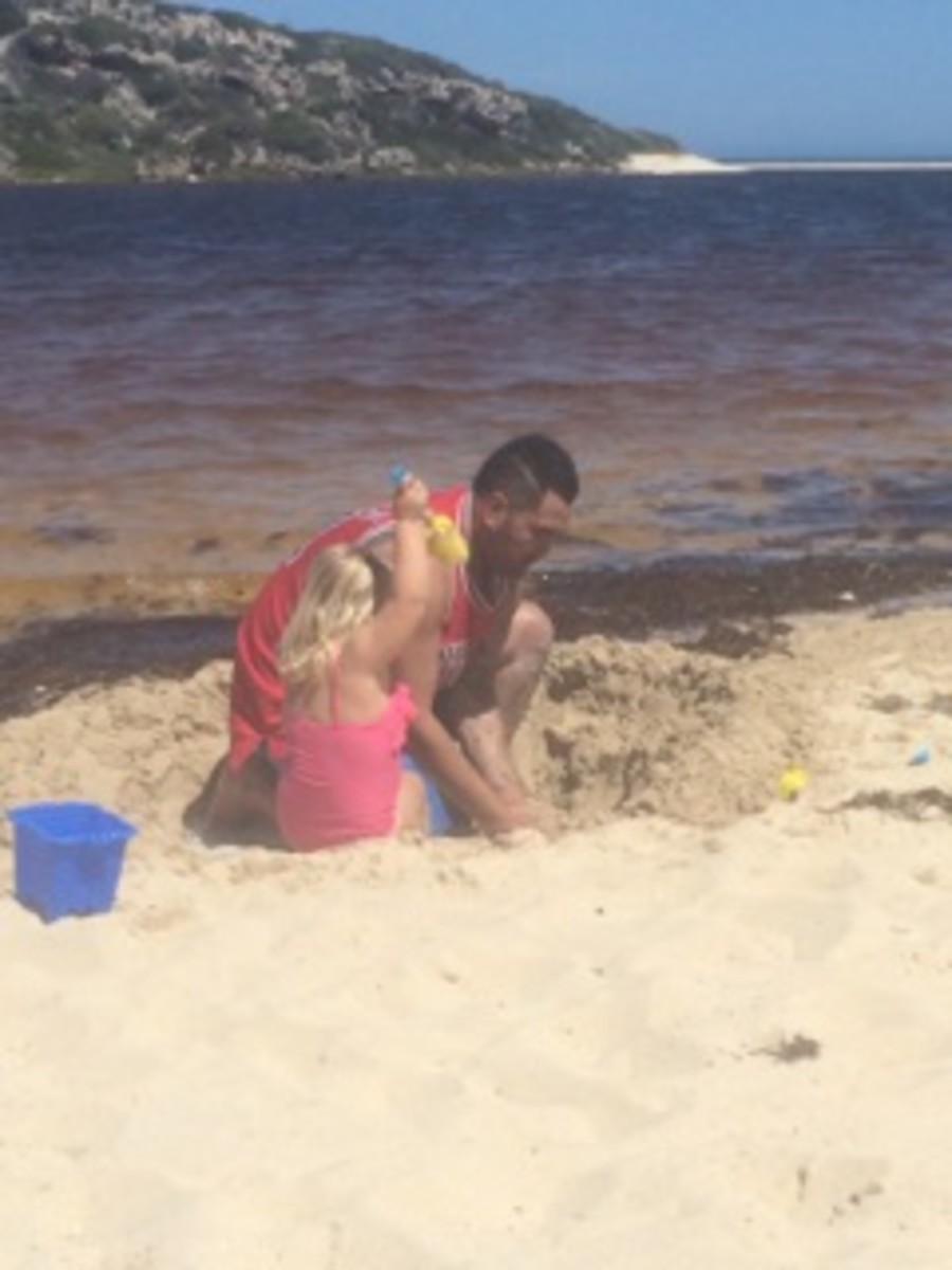 Ko builds sandcastles with his daughter.