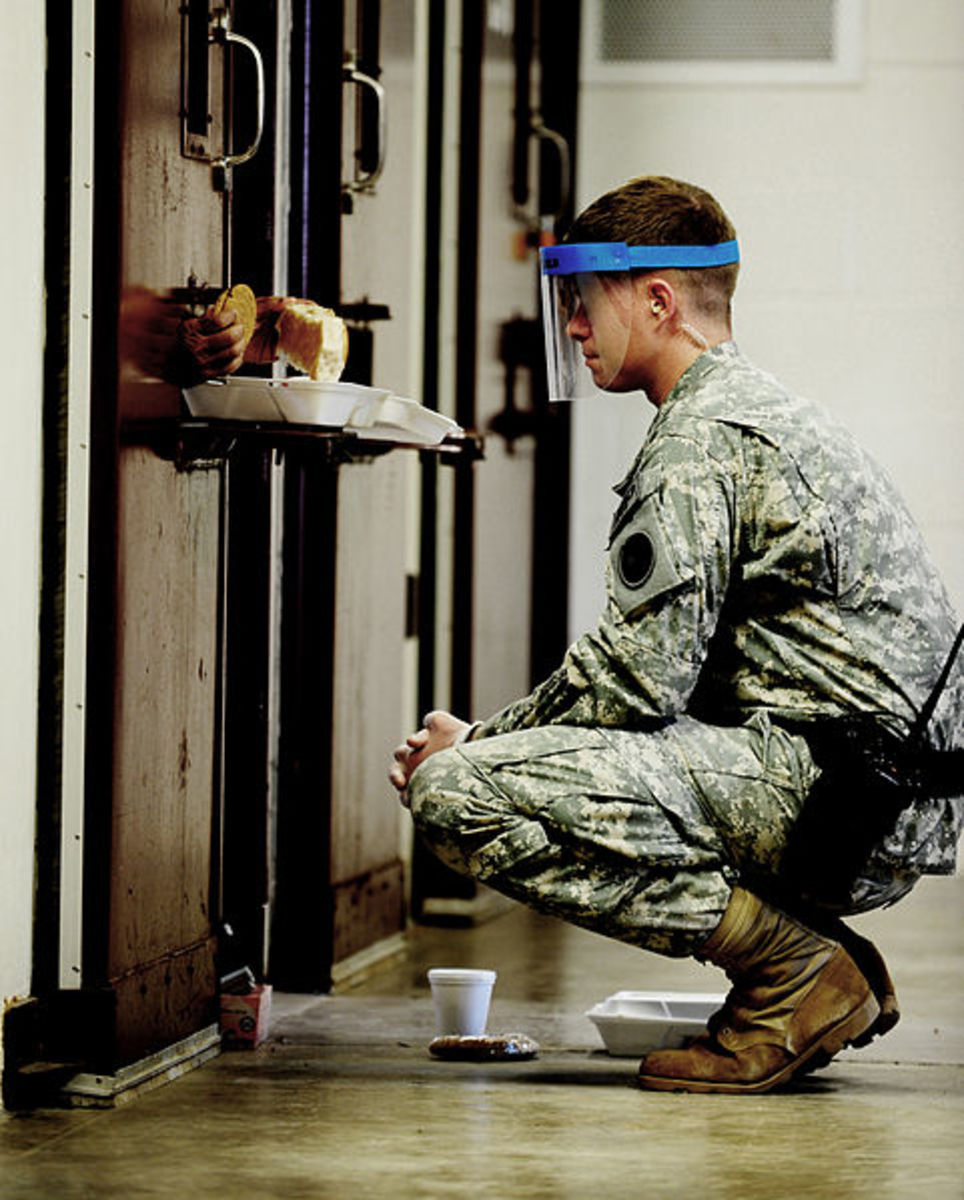 Meal time at Guantanamo Bay. Guards wear masks because sometimes urine or feces will come flying out of the food portal.