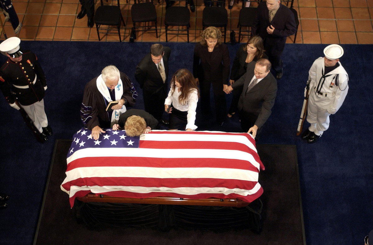 With family members in attendance, Former First Lady Nancy Reagan, lays her head on the flag-draped coffin of her late husband during a service at the Reagan Presidential Library located in Simi Valley, California.