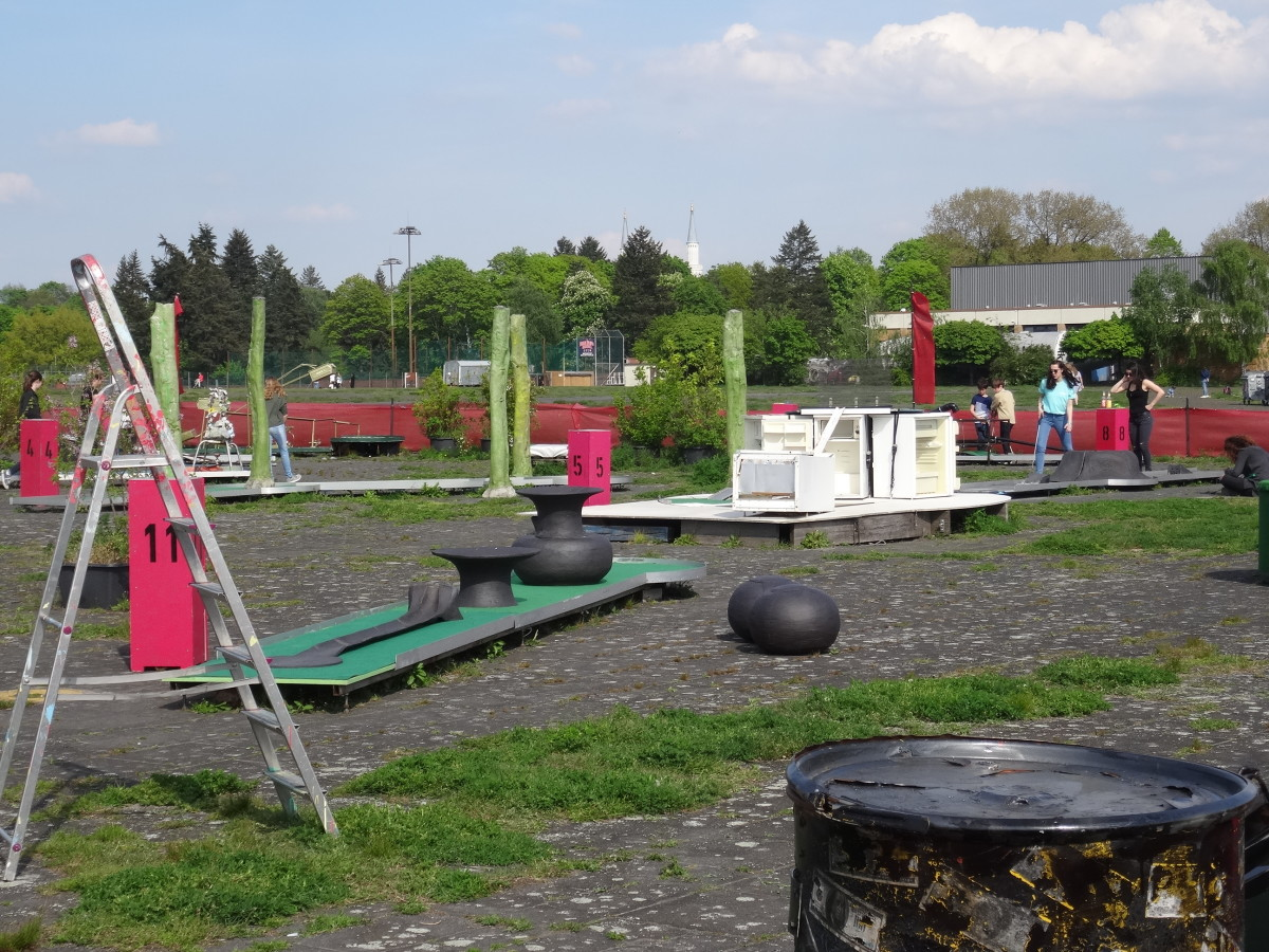 A mini-golf play area, created from scrap metal and sited where once planes parked, sits beneath the minarets, behind the Tempelhofer Feld.