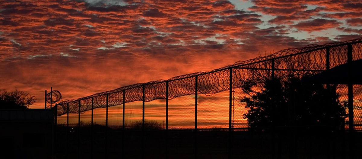 the sunset over a barbed wire fence