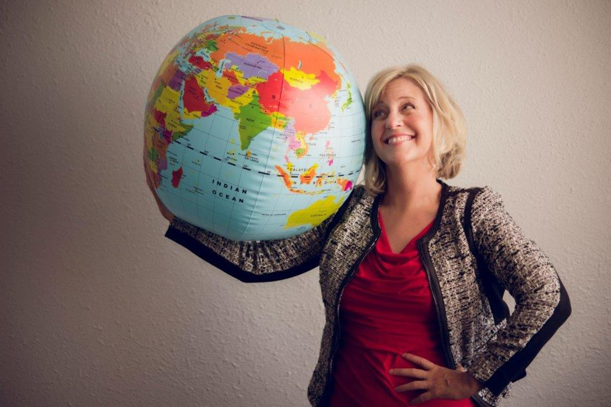 Polly Letofsky posing with globe