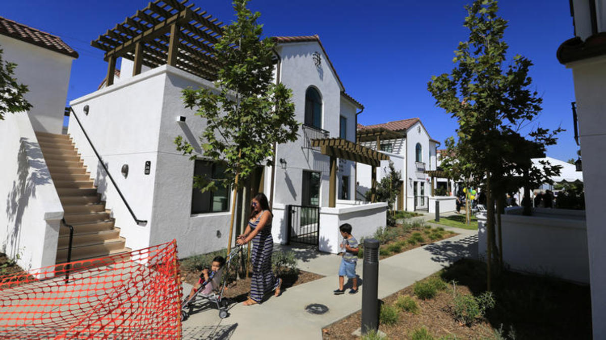 Residents take a stroll through their new complex as city and state officials gather in Vernon on July 25 to celebrate the grand opening of the Vernon Village Park Apartments, a private 45-unit affordable housing development.