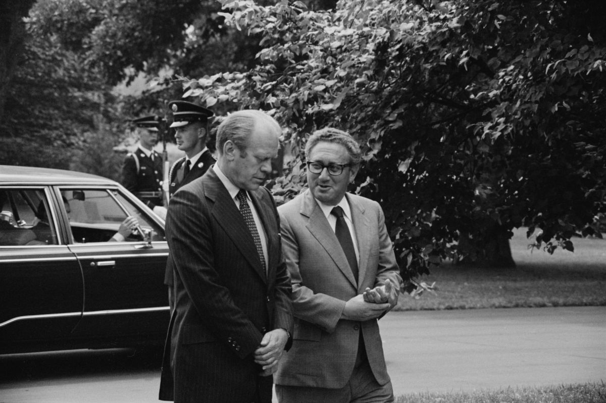 President Gerald Ford and Secretary of State Henry Kissinger, conversing, on the grounds of the White House, Washington, D.C..