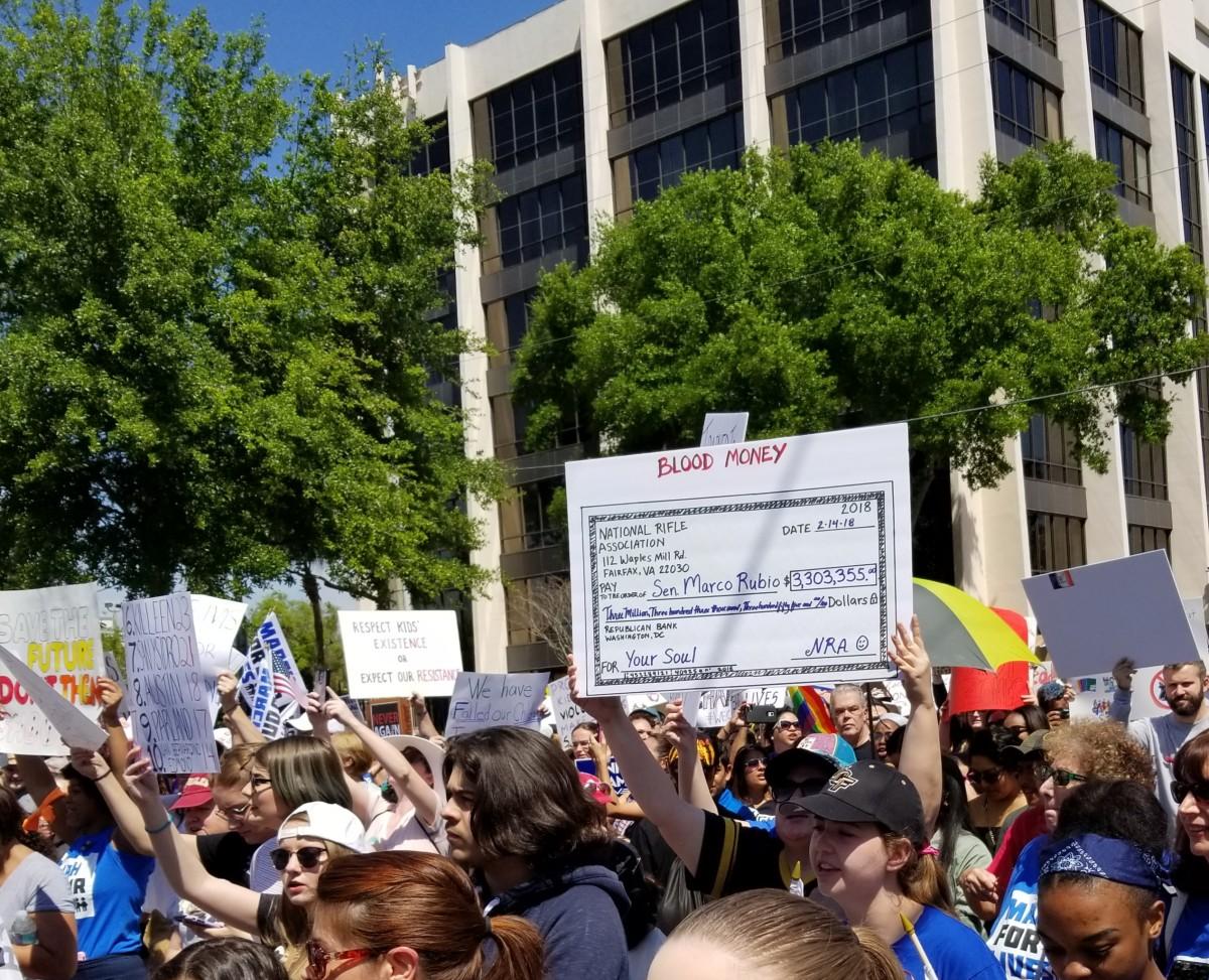 A giant check shows the NRA donations to Senator Rubio.