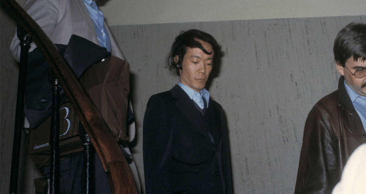 Sagawa being led from the apartment in which he killed Renee.