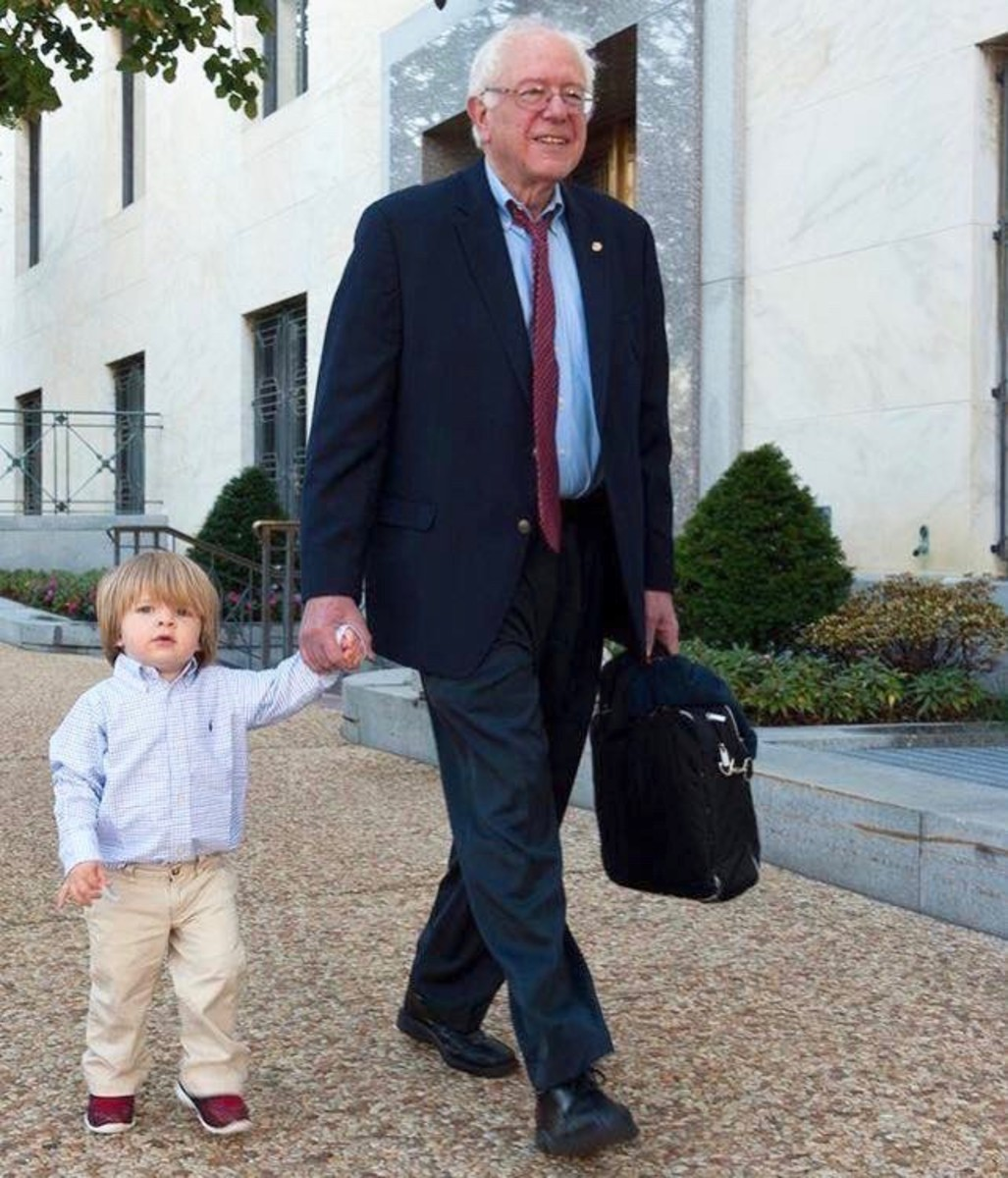 Bernie Sanders walking with one of his seven grandchildren.